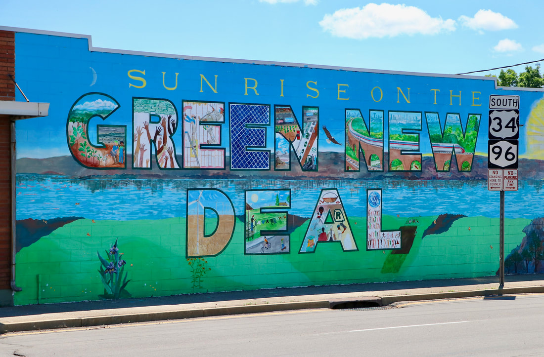 """Dan Burgevin's Mural, """"Sunrise on the Green New Deal,"""" located on the corner of West Buffalo Street and North Fulton Street in downtown Ithaca, NY. (Ithaca Murals)"""