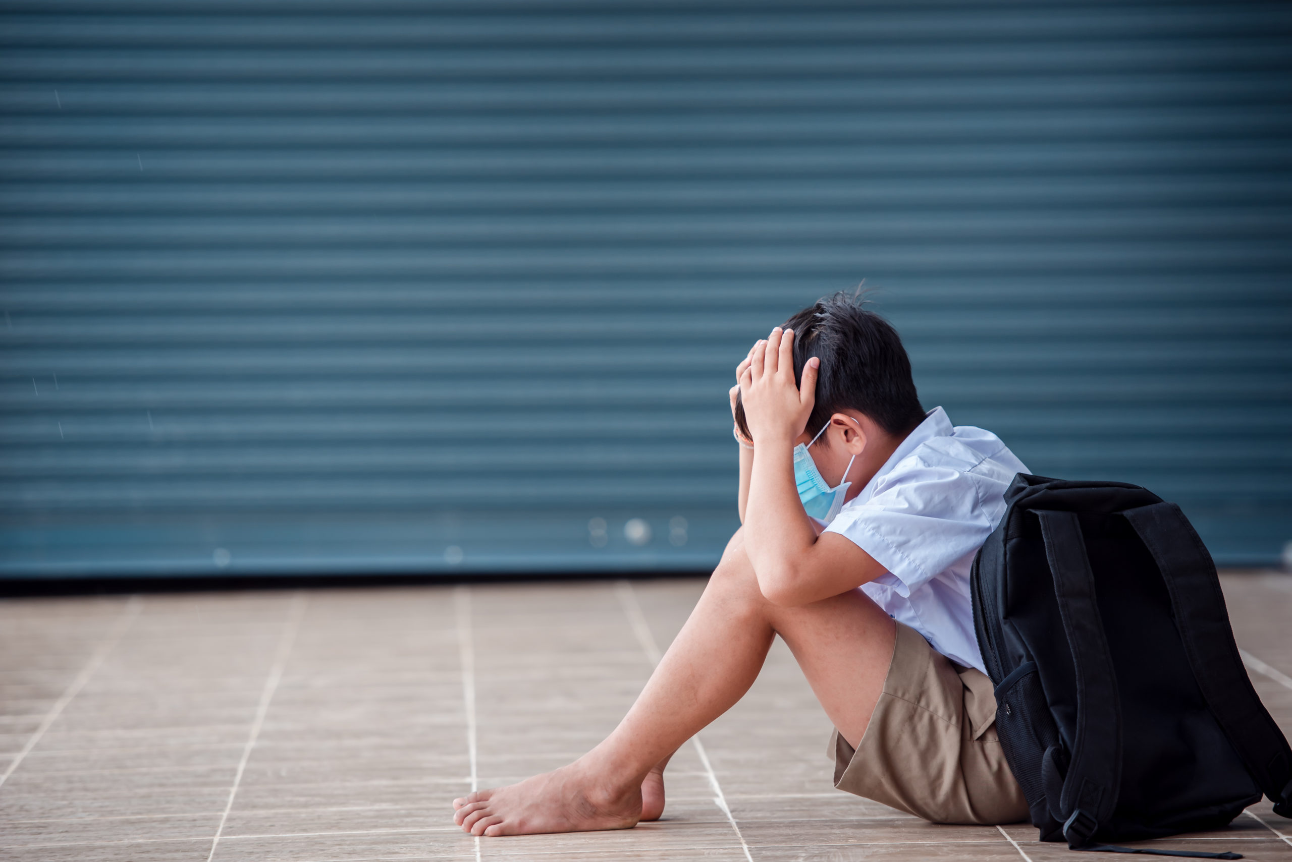 Elementary school asian school children Wearing a medical mask Sad sitting at school